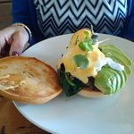 Avocado bagel with poached eggs and hollandaise