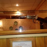 An old rifle hanging in the entryway as you come in.