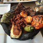 Molcajete: Grilled chicken, steak, chorizo, shrimp, nopalitos, and cheese served in a roasted to