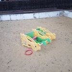 Play area-- broken, tipped over, dirty, garbage and old tiles in sand