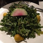 Arugula salad with watermelon radish garnish.