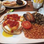 On the left a slcie of toast with two slices of bacon, two fried eggs and two hash browns...