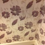 Stained and damp wallpaper lifting off the wall.