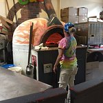 One of our hosts making our brick oven pizza!