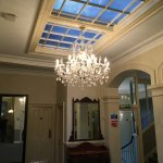 Lovely chandeliers light the reception area, stairs and bar