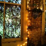 The vine covered windows, when coupled with fairy lights, makes an enchanted room inside.