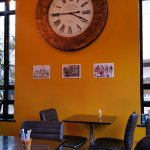 The big clock on the wall inside the cafe.