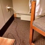heater baseboard missing and more stains on carpet, you can see stains on chair, worn end table