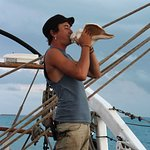 Crew member Noah blowing the conch shell