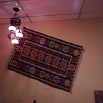 2 neat lighting fixtures and an oriental carpet on the wall