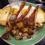 Sunny side up eggs with bacon, home fries and raisin toast