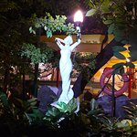 A statue (erected 1958) in the jungle-like garden by the pool of The Atlanta Hotel, Bangkok
