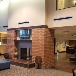 Lobby with fireplace and surrounding breakfast seating area.