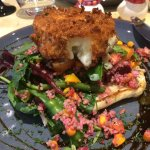 Breaded goats cheese on a bed of beetroot and vegetables. Delicious
