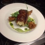 Roast cod fillet wrapped in mint pesto & Serrano ham, crushed potato, crunchy fried prawns .