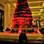 Lunesa F sitting at the base of giant Christmas tree at beautiful and spacious lobby of Westin L