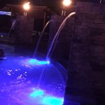 Pool area at night, lights in pool change colour, fire torches a nice touch