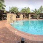 Landscape view of main pool, kids shallow pool, undercover seating lounges, deck chairs, slide &
