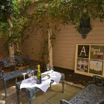 The Hotel Alcott's lush center courtyard is the perfect place to unwind with a bottle of wine