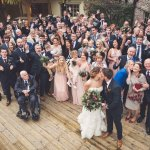 Large group wedding photo on decking area