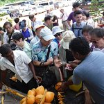 Sanjaya jumps in to help open king coconuts for a tour bus!