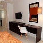 Desk, dresser, TV and charging station at Superior room.