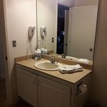 outdated motel type bathroom sink, no real counter space, very small trash can