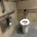 Public restroom in hotel lobby, with compliant grab bars at side and back of commode