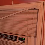 Blinds and air conditioner above the bed