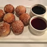 Warm doughnuts with chocolate and raspberry sauces