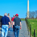 Walking along the sidewalk with the Washington Monument in the background.