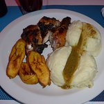 Jerk chicken meal with side of mashed potatoes with gravy and fried plantains