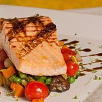 Grilled Atlantic salmon on a bed of vegetables.