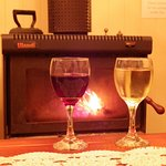 Cosy up with a glass of wine by the fire.