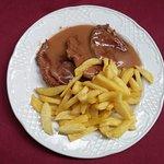 plato de scalopines con salsa de limon y patatas fritas