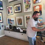 Sean Callahan, gallery owner and artist with his work on the wall behind him