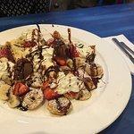 mini pancakes served with vanilla & choc ice cream, strawberries & bananas, whipped cream, and c
