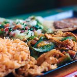 Chicken Fajita served with rice, beans, and salad.