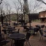 lovely clock tower surrounded by metal tbles nd chairs