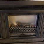 Filthy fireplace in the rooms. Can't even see the fire through the dirty glass.
