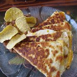 The quesadilla with refried beans and the tortilla chips standing in the beans