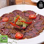 Beef and  Biltong Carpaccio, drizzled with homemade chimichurri sauce