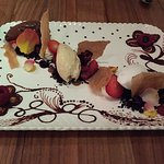 Ice cream, sorbet, chocolate and fruit dessert plate for two with cholocate decorated plate