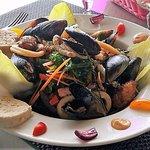 Assiette de la mer, a base de moules, calamars sur lit de salade et algues, accompagné dune terr