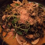Squid ink pasta with squid, clams, lobster in a briny, saffron broth