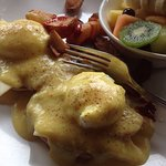 Eggs Benedict with home fries, coffee, and fruits breakfast