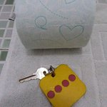 Toilet paper with green hearts, and four-dot room key, on bathmat