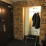 Entrée de la chambre avec espace pour ranger les manteaux et support pour la valise.