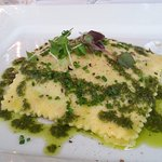 Nettles Ravioli with sweet sheep cheese, whole egg, on bed of sauteed greens