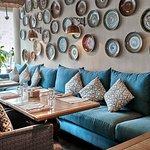 Стена украшена тарелками с уютным диваном